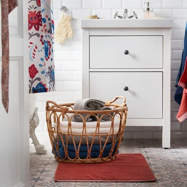 IKEA SNIDAD rattan basket is standing on a bath mat in the bathroom and is storage for fresh and folded towels.