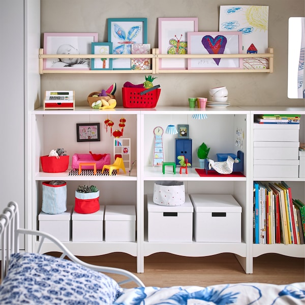 IKEA SOLGUL white changing tables side by side, customised as an open shelving unit, displaying toys, boxes and books.