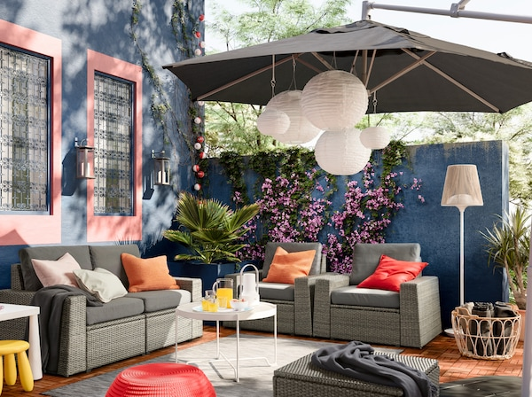 IKEA SOLLERÖN outdoor seating solution with removable dark grey covers in a colourful outdoor space with deep blue walls.