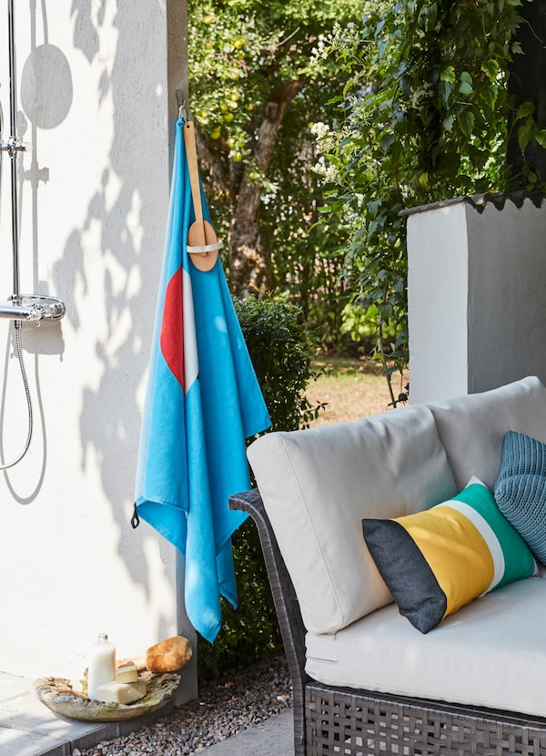IKEA SOMMAR 2019 bright blue beach towel hanging next to an outdoor shower.