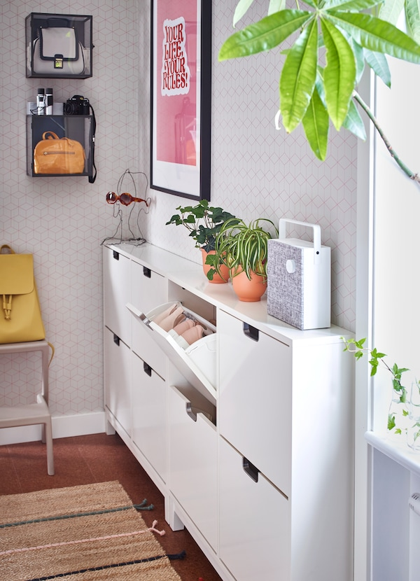 IKEA STÄLL white shoe cabinet comes with four compartments that can hold up to two pairs of shoes per compartment. Tilt open the shelf by pulling on the square-shaped slot.