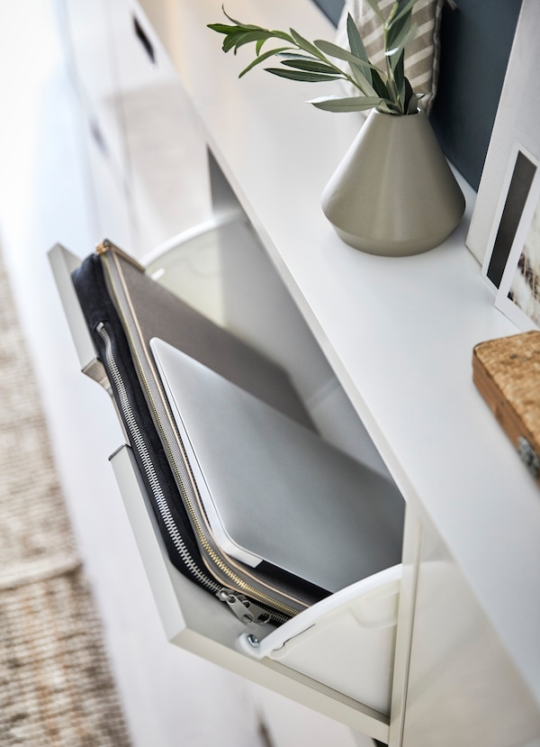 IKEA STÄLL white shoe storage cabinets, open to show a laptop and laptop case inside.