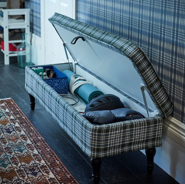 IKEA STOCKSUND blue, green and white plaid patterned long bench has dark wooden legs for a traditional feel and a closed storage compartment when lifted.