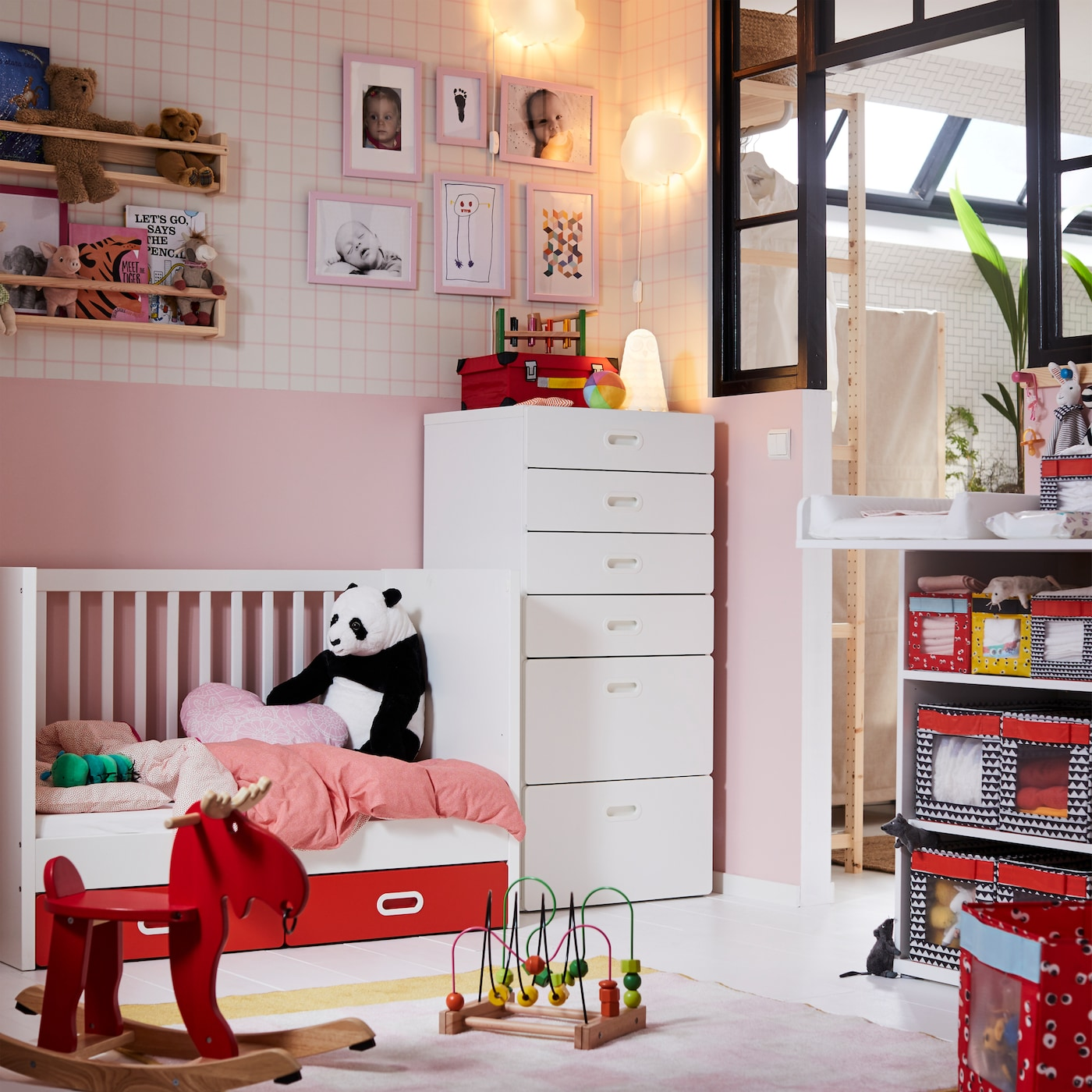 IKEA STUVA white baby furniture crib and six drawer unit in a pink children's nursery room with toys and stuffed panda bear.