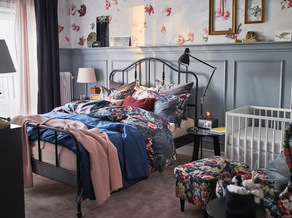 IKEA STUVA white cot and changing table, with SAGSTUA black bedframe in a small bedroom with vintage floral wallpaper.