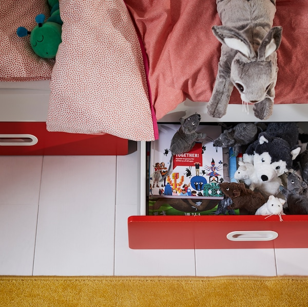 IKEA STUVA white cot with two drawers holding storybooks and stuffed animals.