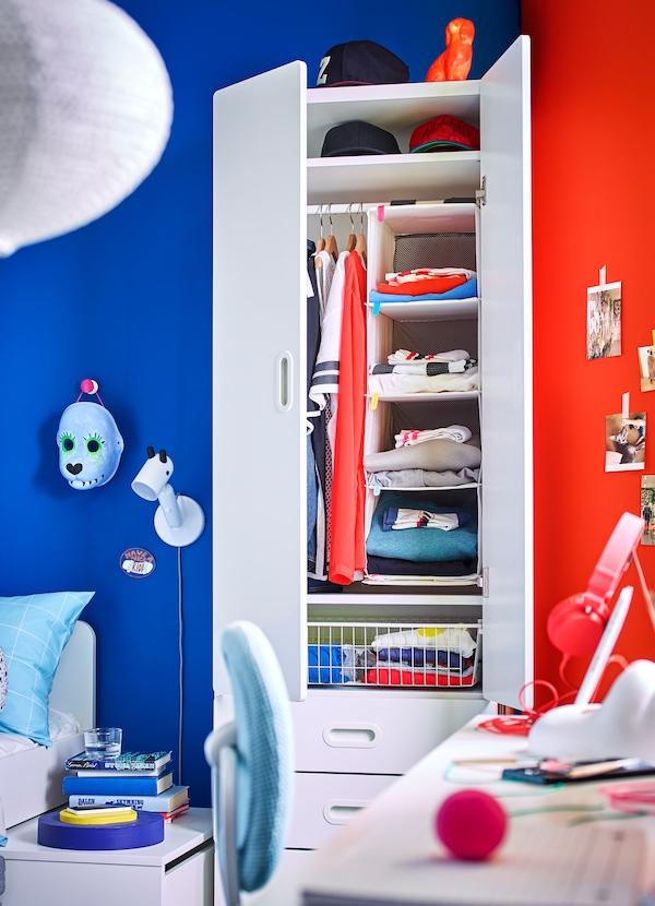 IKEA STUVA white wardrobe with RASSLA hanging storage organiser and folded clothes.