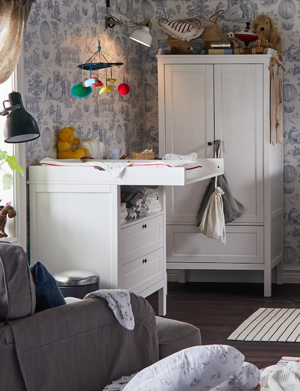 IKEA SUNDVIK changing table in a room with floral wallpaper, wardrobe, armchair, mobile and baby nursing items.
