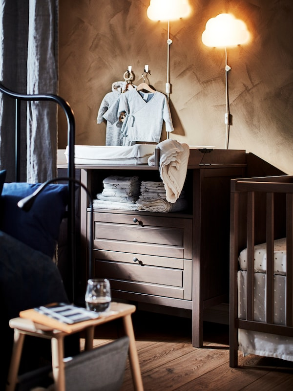 IKEA SUNDVIK changing table in dark wood with baby clothes and baby linens, cot and small side table.
