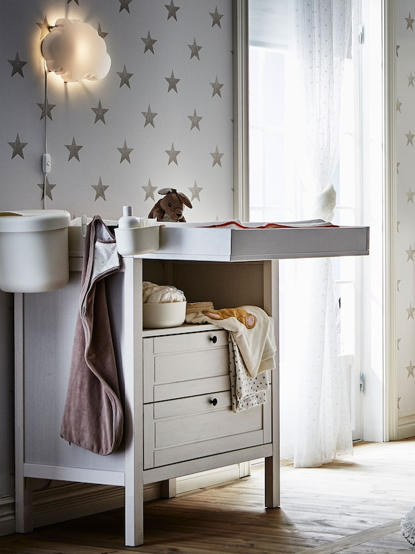 IKEA SUNDVIK changing table in white with baby clothes and baby linens, crib and small side table.