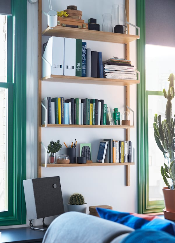 IKEA SVALNÄS bamboo wooden wall mounted shelf holding books and papers on 4 shelves.