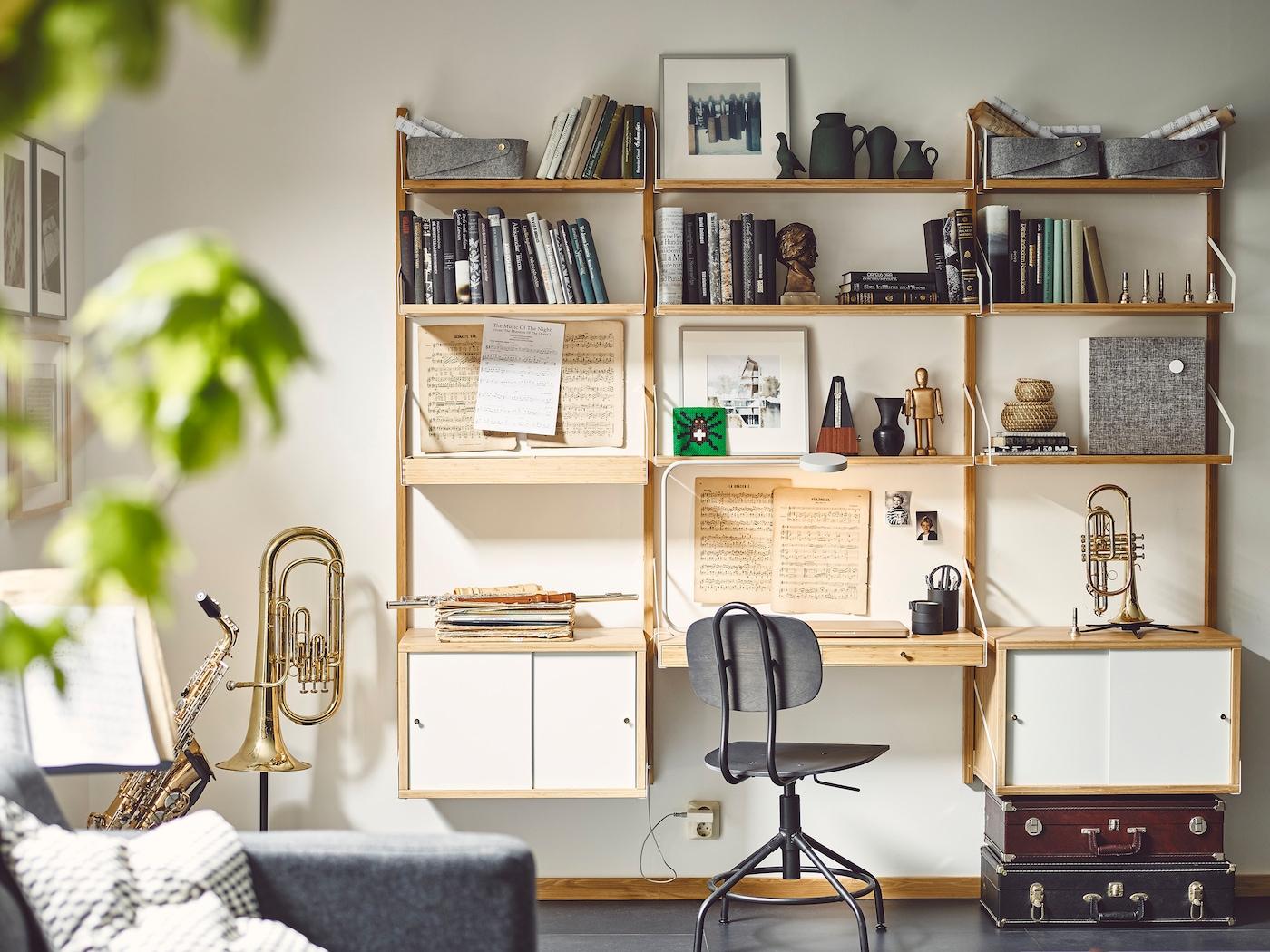 IKEA SVALNÄS vägghylla på en vit vägg i ett vardagsrum. Hyllor och skåp med personliga samlingar och böcker. En skrivbordsstol framför SVALNÄS skrivbordsskiva.