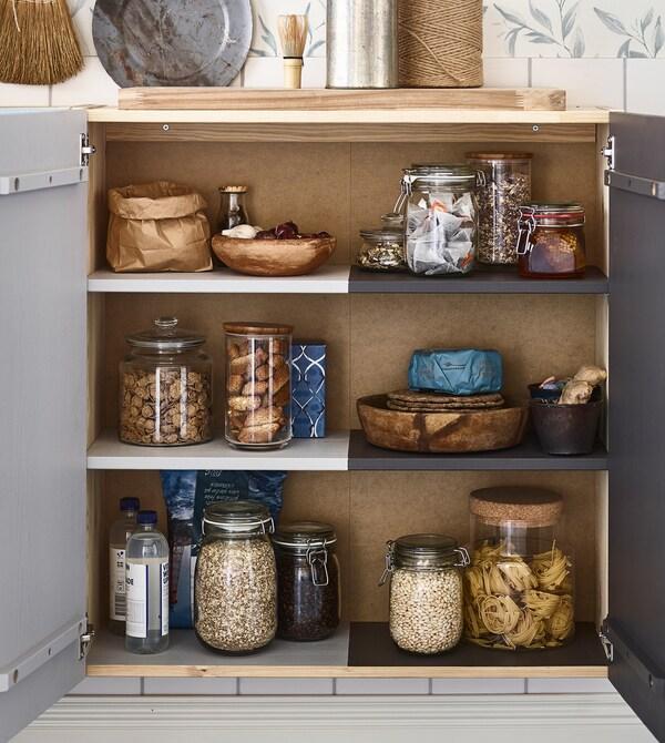 IKEA taldeko IVAR armairua biltegiratzeko poteekin, margatuak, janari lehorrarekin, alde bakoitzaren jabea nor den erakusteko.