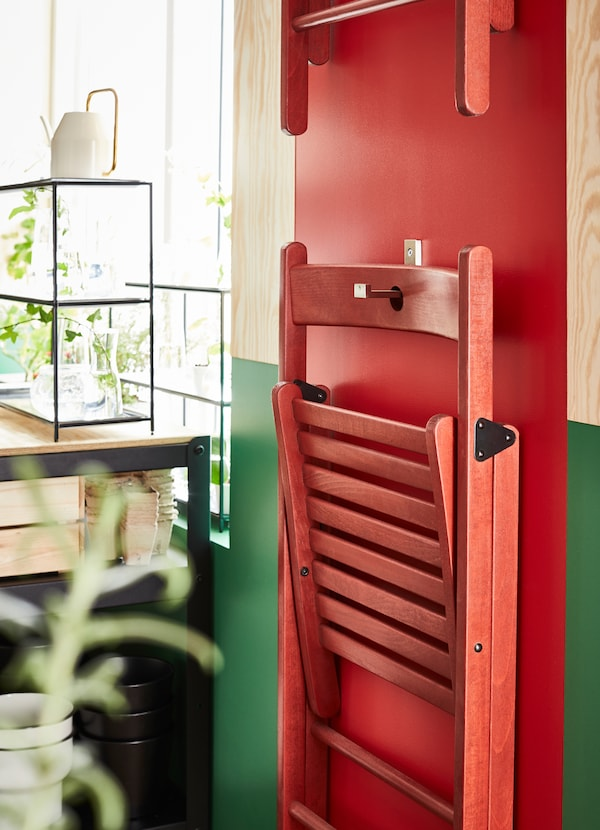 IKEA TERJE red folding chairs have a small carved hole in the backing so you can hang them on the wall on a BJÄRNUM stainless steel mounted hook.