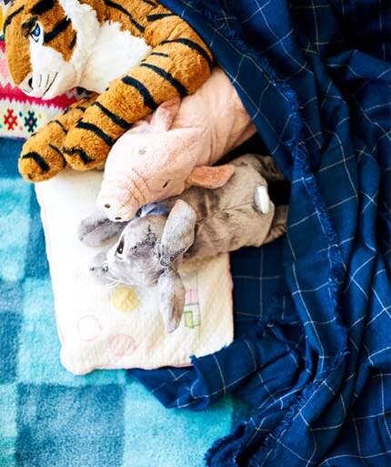 ikea-tiger-and-pig-soft-toys-for-kids-under-a-varkrage-throw-on-a-blue-stillsamt-rug