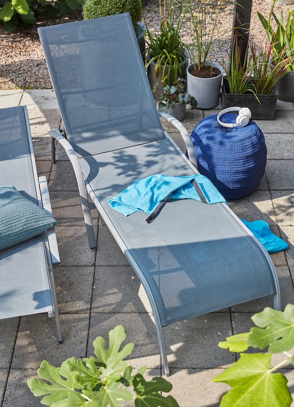 IKEA TORHOLMEN grey mesh lounge chairs weaved from grey polyester fabric with a blue knitted pouffe on the side.