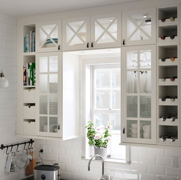 IKEA TORNVIKEN white kitchen cabinets with vitrine doors with a wooden cross across the unit.