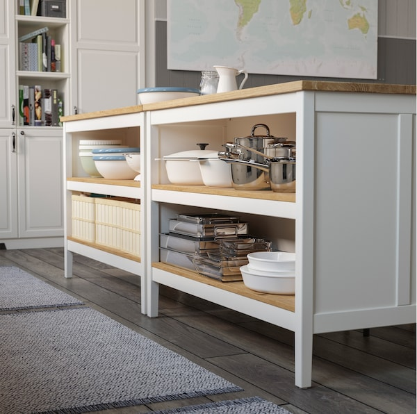 IKEA TORNVIKEN white kitchen island comes with traditional light wooden inner shelves. One side has storage space for pots, while the other is for seating.