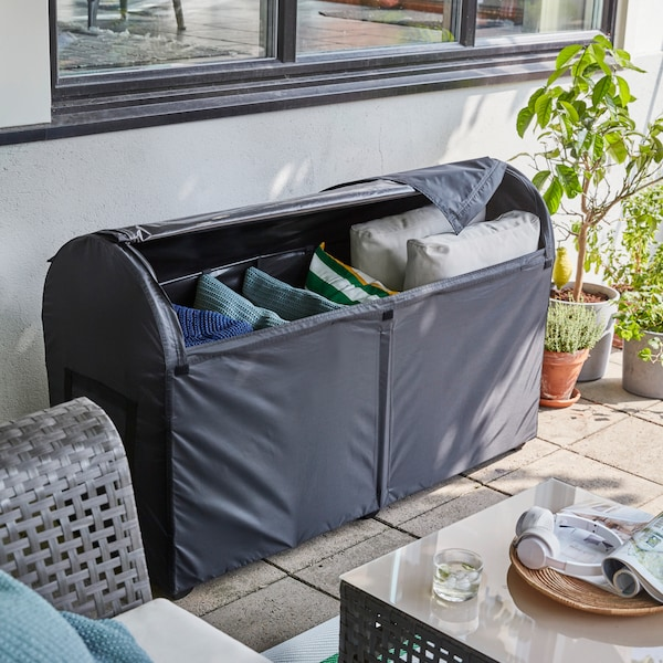 IKEA TOSTERÖ weatherproof black storage box unzipped to show stowed cushions.