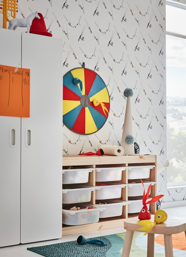 IKEA TROFAST pine and white plastic drawers and LUSTIG dartboard are children's storage and playtime in one. The lightweight soft toy squids are easy to throw.