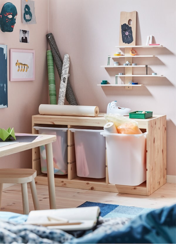 IKEA TROFAST pine storage cabinet with three deep plastic bins storing stationary and creative supplies.