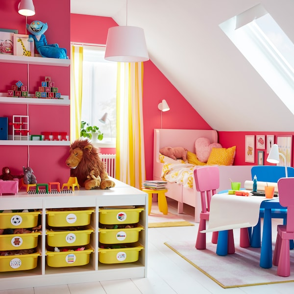 IKEA TROFAST white storage combination unit with nine yellow plastic bin shelves in a bright pink children's room.