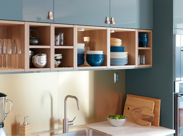IKEA VADHOLMA dark brown ash veneer open storage shelves integrated above a kitchen sink, holding bowls and glassware.
