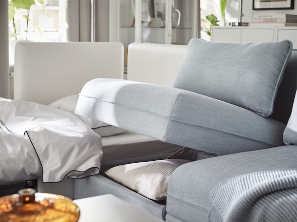 IKEA VALLENTUNA blue sofa unit with storage compartment propped open to reveal bedlinens and pillows.