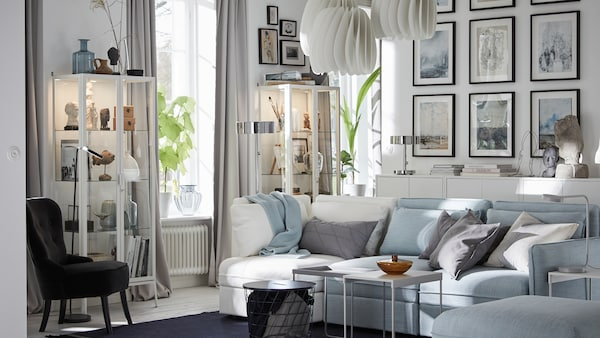 IKEA VALLENTUNA light blue and white modular 3-seat sofa in a living room with diverse items displayed on shelving.