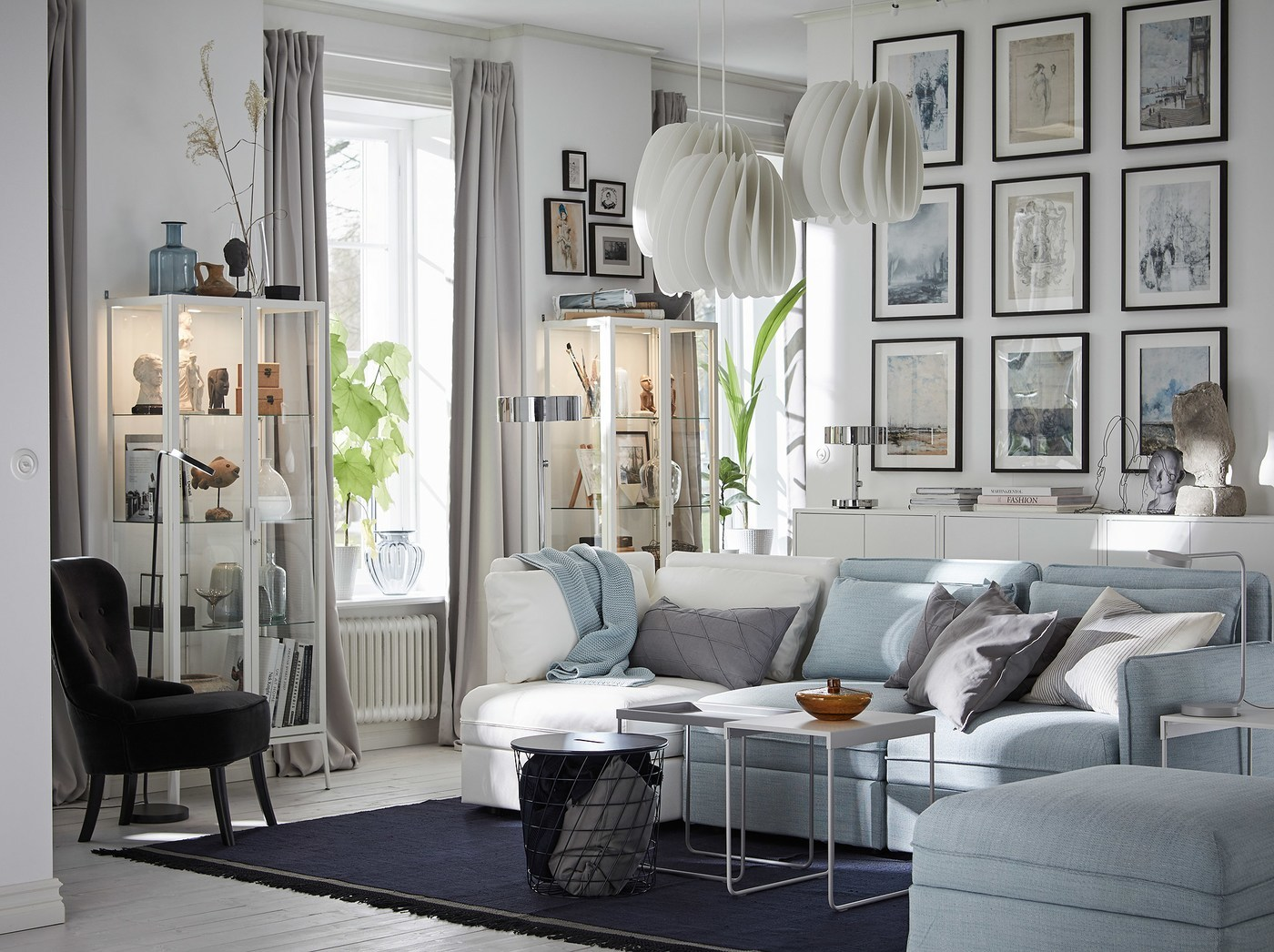 IKEA VALLENTUNA light blue and white modular sofa combined to make a 3-seat sofa in a living room with many picture frames and displayed items in MILSBO glass cabinets.