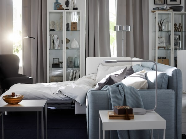 IKEA VALLENTUNA white and blue modular sofa unit, extended out into a sofa bed.