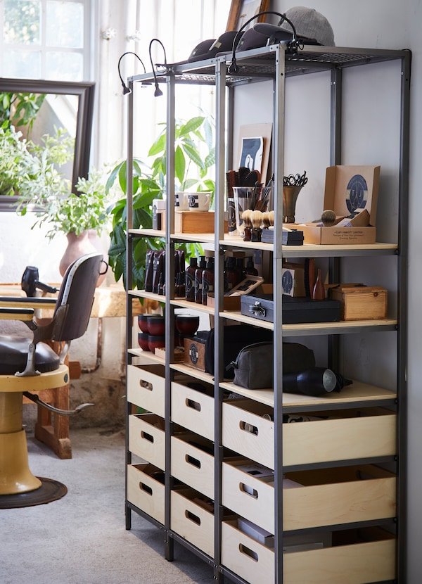 IKEA VEBERÖD shelving unit with black frames and natural wooden shelves, with barber products displayed on top.