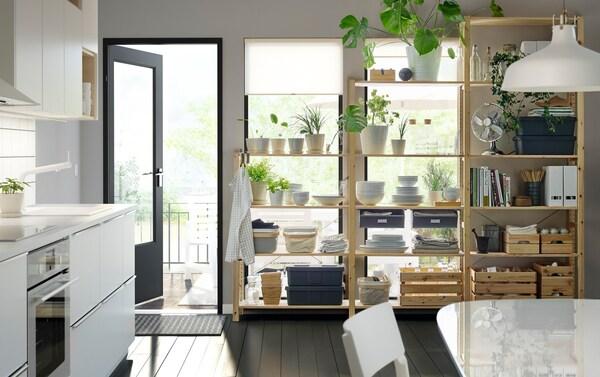 IKEA VEDDINGE modern matte white monochrome kitchen with plants, dinnerware and files on IVAR wooden shelves, door towards the garden is open.