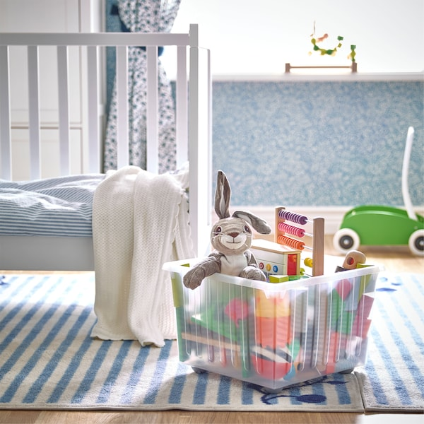 영아용 장난감이 들어 있는 IKEA VESSLA 베슬라 화이트 이동식수납상자가 유아용 침대 옆의 블루와 화이트 색상의 줄무늬 러그 위에 있는 모습