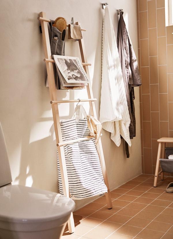 IKEA VILTO birch shelving unit leaning against a wall in a bathroom.