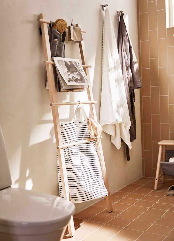IKEA VILTO birch shelving unit leaning against a wall in a bathroom.