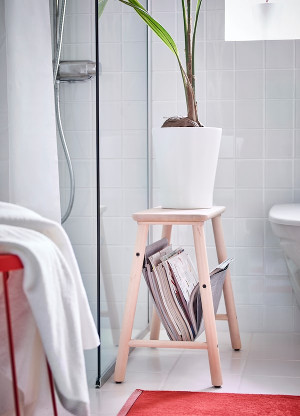 IKEA VILTO light birch wood storage stool is 45 centimeters in height and has a grey felt sling underneath the seat to store magazines and books in the bathroom.