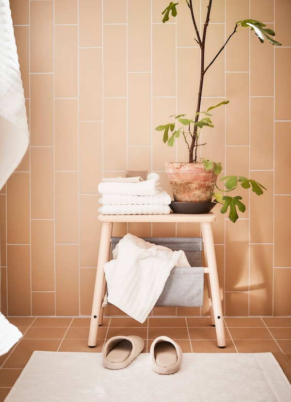 IKEA VILTO step stool with a potted plant and white hand towels on top.