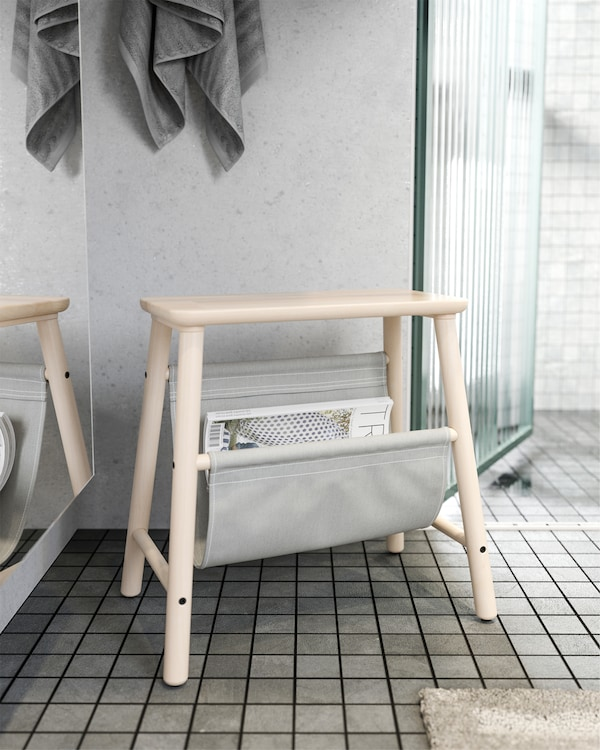 IKEA VILTO stool in birch that's standing outside the bathroom and it stores magazines in the grey fabric.