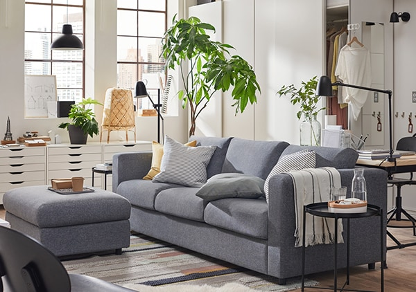 IKEA VIMLE 3-seat sofa-bed Gunnared medium grey decorated with cushions at a living room and s footstool.