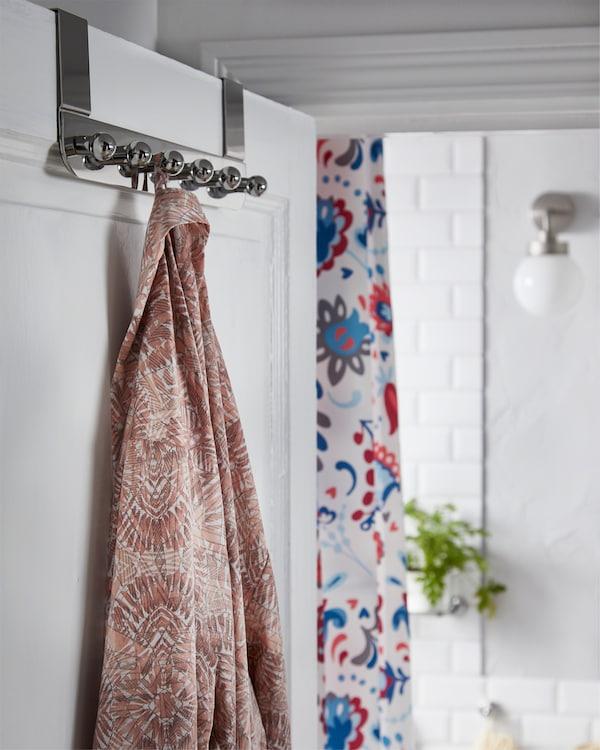 IKEA VOXNAN hanger for the door in chrome effect hangs on the bathroom door and a morning robe is hanging on it.