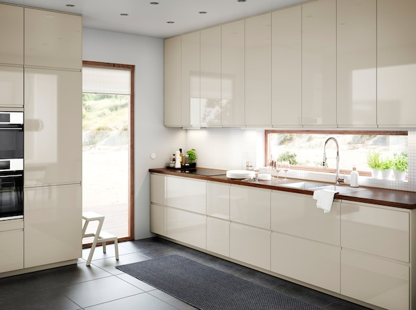 IKEA VOXTORP light beige high-gloss kitchen cabinet doors and kitchen drawers with walnut worktop in a large modern kitchen.