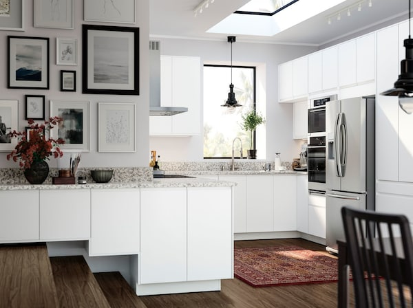 IKEA VOXTORP white kitchen cabinets and white cabinet door fronts that work around a small kitchen with steps and ledges.