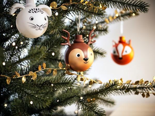 IKEA Weihnachtsdekorationskugeln in Form eines Hasenkopfes, eines Hirschkopfes und eines Fuchskopfes, und Lichterkette am Baum.