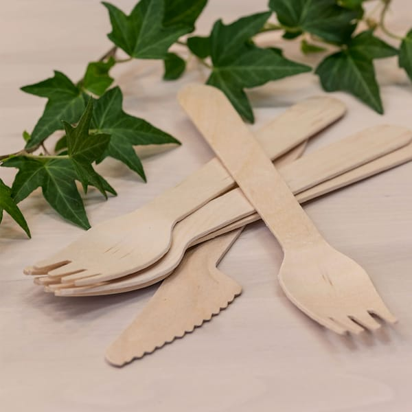 IKEA wooden fork and knife disposables lying on a wooden bench.
