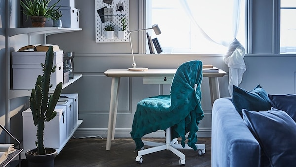 IKEA workplace in the living room with a storage system against the wall