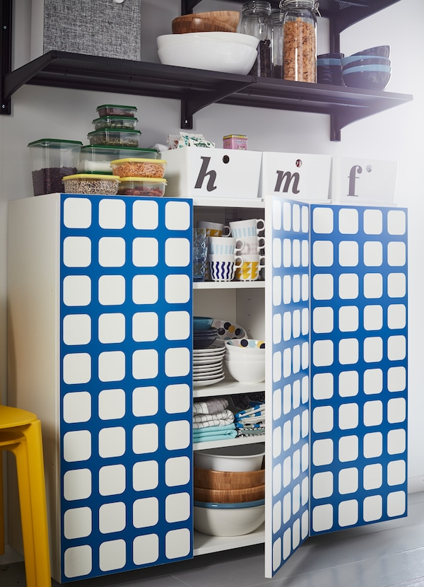 IKEA YTTERBYN kitchen cabinet door fronts come in bold colours and patterns designed by Swedish collective 10-gruppen. One pattern includes a bright blue grid pattern on a white base.