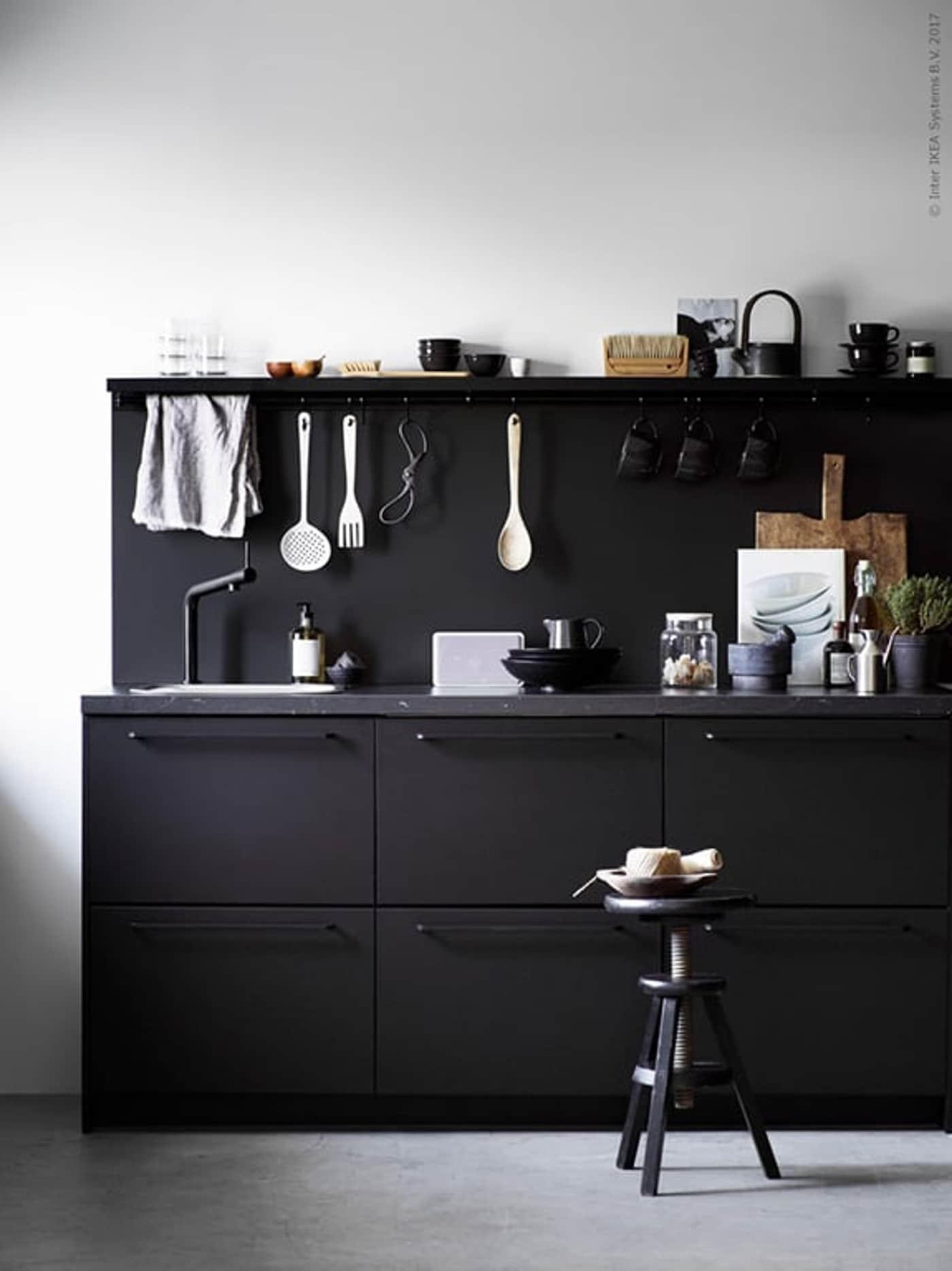 IKEA zwarte keuken met keukenaccessoires en kruk