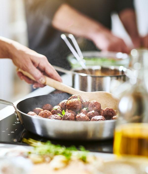 イケアのHUVUDROLL/フヴドロル プラントボールをステンレススチール製フライパンで調理し、木製スプーンでかき混ぜているところ。