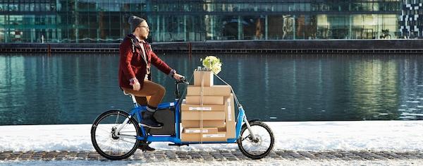 イケアのパッケージを積んだカーゴバイクに乗る男性。